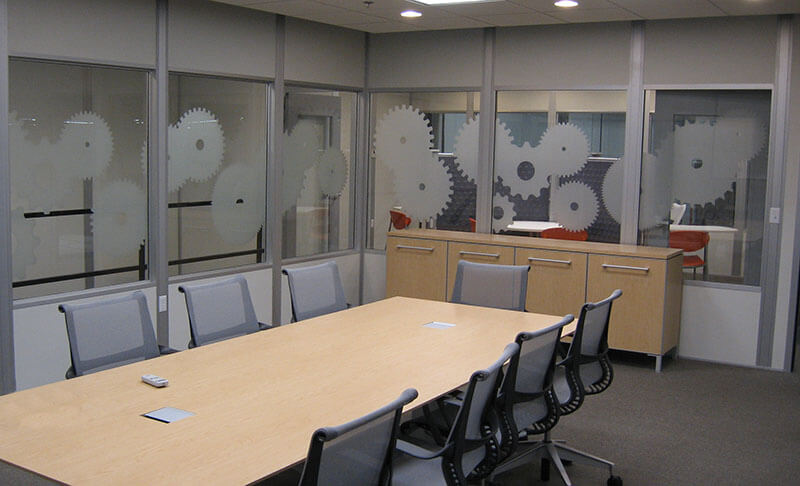 Conference room interior of modular office with gear art on glass